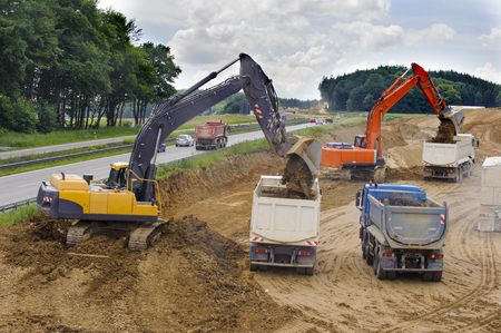german highway under construction with trucks and digger