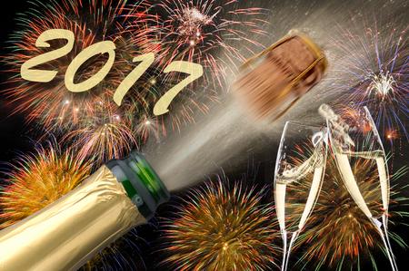 祝賀会: 飛び出るシャンパンと 2017 年の大晦日の花火 写真素材