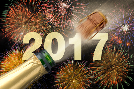 new years eve background: popping champagne and fireworks at new years eve 2017