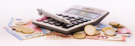 Many Euro banknotes and calculator laying on table Standard-Bild
