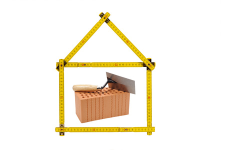 building regulations: house and construction company with brick and folding rule