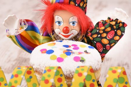 clown with red hairs and sweet donut at carnival Stock Photo