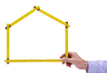 Meter-Regel gefaltet als Haus in der Hand von Immobilienmakler Standard-Bild