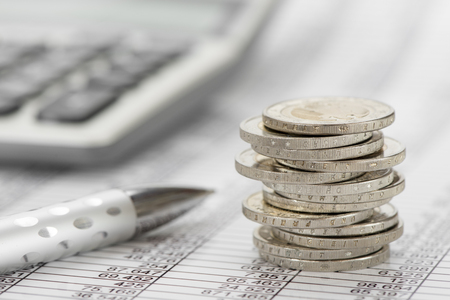 hoja de calculo: stacked euro coins on table sheet with chart of exchange market Foto de archivo