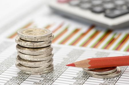 Gestapelde euromunten op tafelblad met grafiek van beursmarkt Stockfoto
