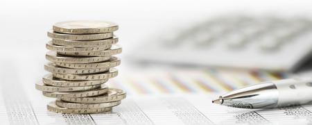 ułożone monety nad danymi z rynku akcji z kalkulatora