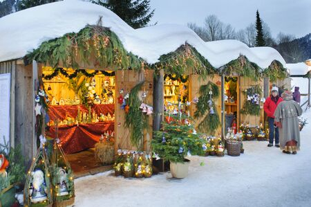 romantic christmas market in Bavaria with illuminated and decorated wooden huts in snow