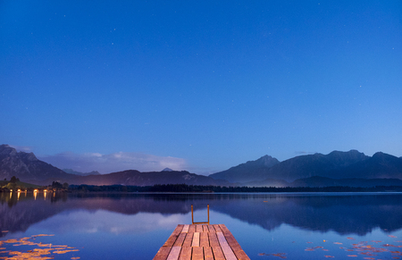 twilight at lake Hopfensee in Bavaria with pier and mountains mirroring in water