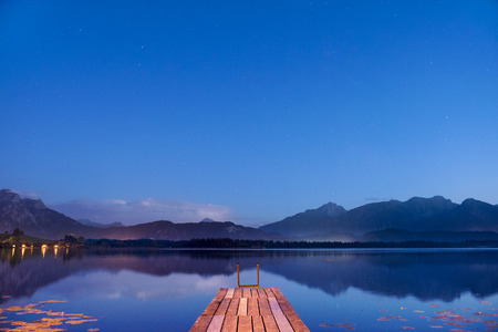 sunset at lake with mountains and wooden pier in Bavaria, Germany Stock Photo