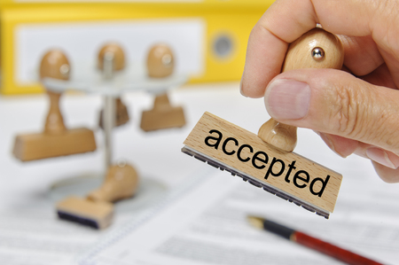 accepted printed on rubber stamp holding in hand