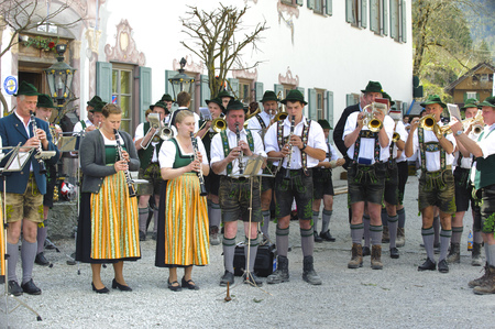 In many villages of Bavaria it is historical customs to erect an decorated high tree at 1. May by local men, clothed in traditional bavarian dress with short leather trousers and white shirt. While other local men are working to put up the tree, a Bavaria