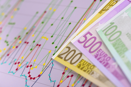 banknotes of European currency laying on chart of stock market Stock Photo