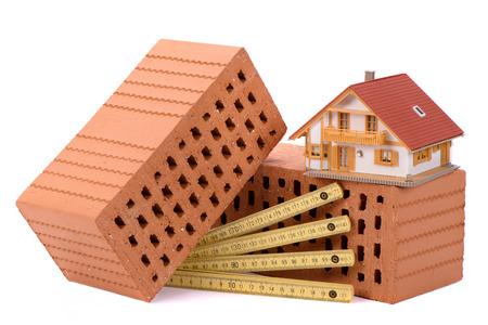 Construcción de casas con ladrillo, herramientas, plan y modelo de casa. Foto de archivo