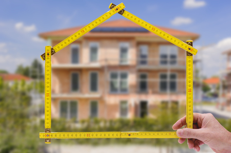 yardstick folded in form of an house in hand of an agent