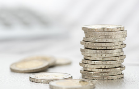 stacked coins of european currency with data of stock market and calculator