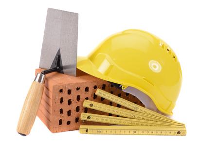 Hausbau mit Ziegeln, Werkzeugen, Plan und Modellhaus