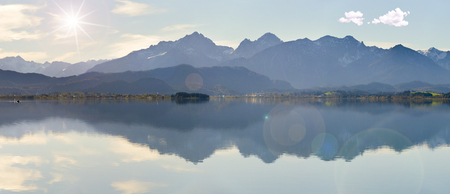 wide angle view to alps mountain range mirroring in lake Forggensee in region Allgaeu in Bavaria Stock Photo
