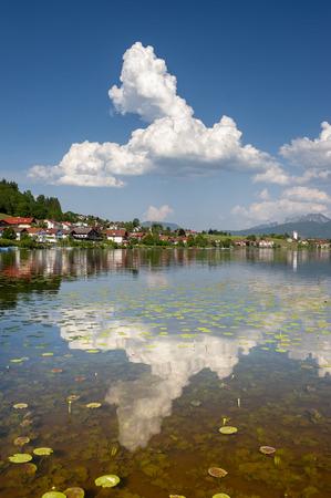 clouds mirroring in lake Hopfensee in Bavaria