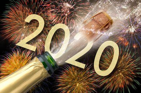 Felice anno nuovo 2020 con fuochi d'artificio e spruzzi di bottiglia di champagne