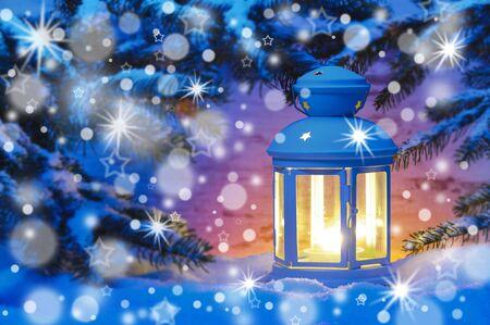 Laterne mit Kerzenlicht im Schneefall an Weihnachten