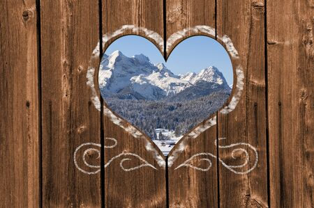 Looking through a carved heart in a wooden wall to the Zugspitze mountain in Bavaria, Germany