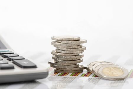 stacked coins of European currency nearby calculator