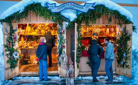 Ettal, Germany / Bavaria - December 31, 2019: Snowy Christmas market with illuminated shops in wooden huts with gifts and handmade decoration.