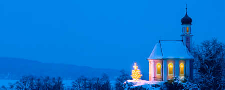 romantic Christmas chapel with illuminated tree in snow on hill Imagens