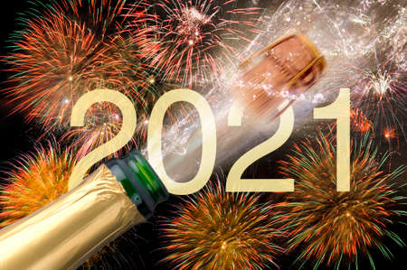 popping bottle of champagne with firework at silvester 2021
