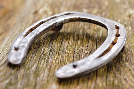 old horseshoe laying on wooden plank