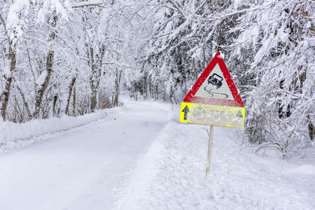 road sign warns of ice and snow at winter