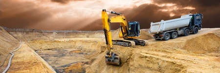 excavator working on construction site with dramatic sky