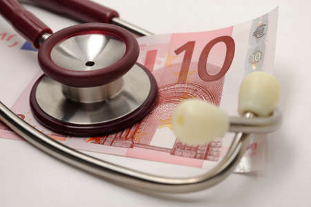 Costs and revenues in the health sector with euro banknote and stethoscope Stock Photo