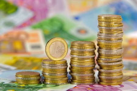 Euro banknotes and stacked coins Stock Photo