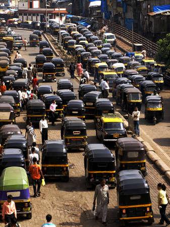 contaminacion acustica: MUMBAI, INDIA-JULIO 17, 2008: Multitud y atasco en el local de la calle exterior. La calle está llena de auto rickshaws clásicos en Mumbai, India. Editorial