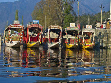 KASHMIR, INDIA-APRIL 10, 2009: Dal lake, the tourist attractive destination in northern India. People use Shikara for traveling and transportation in the lake.