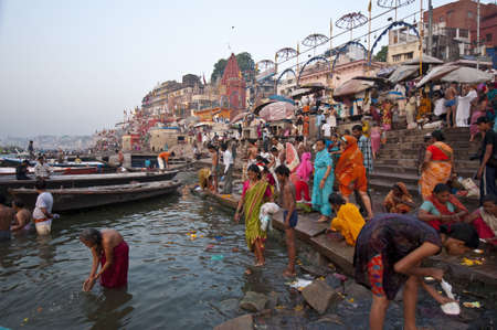 VARANASI, INDIA - APRIL 18, 2010: Crowding of local Indian people live their morning life with Ganga river in Varanasi, India. The most holy river of India and Hindu culture.