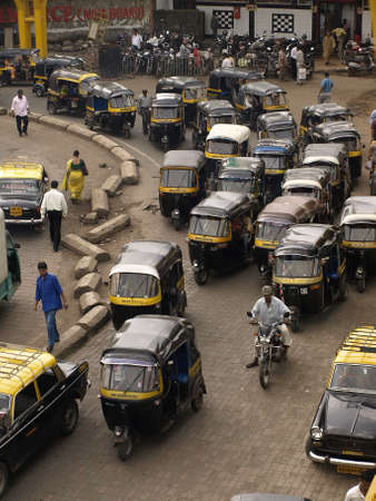 MUMBAI, INDIA-JULY 17, 2008: Crowd and traffic jam on the outer local street. The street is full with classic auto rickshaws in Mumbai, India. Editorial