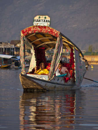 KASHMIR, INDIA-APRIL 10, 2009: Dal lake, the tourist attractive destination in northern India. People use Shikara for traveling and transportation in the lake in Kashmir, India. Stock Photo - 17147035