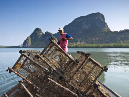 PANYI, THAILAND-FEBRUARY 7, 2009: A fisherman uses the net trap for capturing the wild sea fish in Panyi, Thailand. Panyi island is the unique floating community in south Thailand.