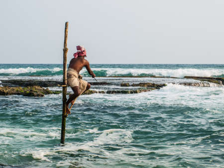 AHANGAMA, SRI LANKA-OCTOBER 23, 2009: The local fisherman is fishing in unique style. The standing on the single timber pole can only found in this Indian ocean in Ahangama, Sri Lanka.