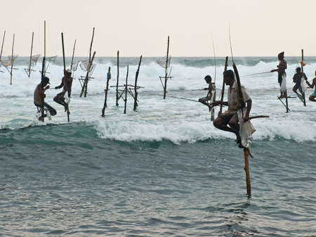 KOGGALA, SRI LANKA-OCTOBER 22, 2009: The local fishermen are fishing in unique style. The standing on the single timber pole can only found in this Indian ocean in Koggala, Sri Lanka.