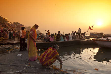 VARANASI, INDIA - APRIL 18, 2010: Crowd of local Indian people live their morning life with Ganga river in Varanasi, India. The most holy river of India and Hindu culture.