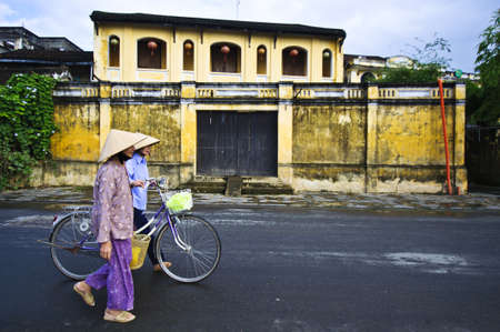 HOI AN, VIETNAM-DECEMBER 7, 2011: Local Vietnamese people are walking along the serene street in Hoi An, Vietnam. Hoi An is the renown of World heritage cultural site.