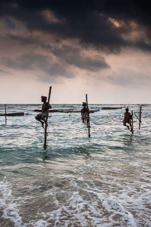 AHANGAMA SRI LANKAOCTOBER 23: The local fishermen are fishing in unique style. The standing on the single timber pole can only found in this Indian ocean on October 23 2009 in Ahangama Sri Lanka. Editorial