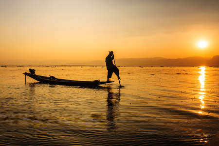 inle: A local fisherman is fishing by boat, Inle lake, Myanmar. Stock Photo