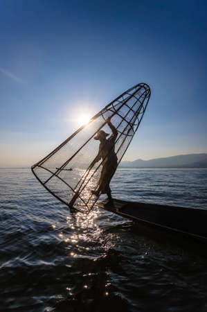 fishing catches: A local fisherman is fishing by boat with bamboo trap, Inle lake, Myanmar. Stock Photo