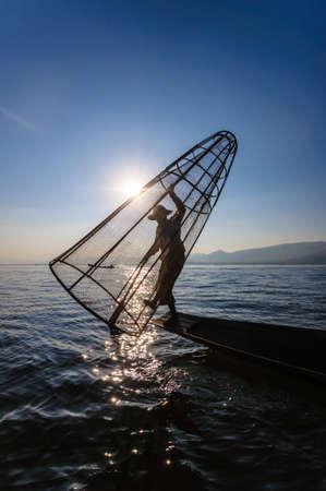 redes de pesca: Un pescador de la zona es la pesca en barco con trampa de bamb�, lago Inle, Myanmar.