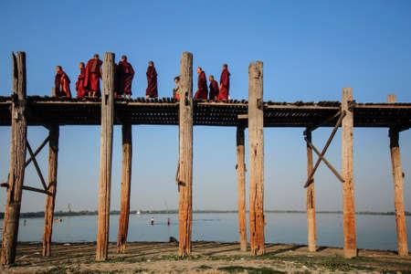Mandalay, Myanmar-JANUARY 6: The Burmese monks are walking across U Bein bridge. The longest teak footbridge of the world on January 6, 2014 Editorial