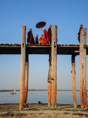 longest: Mandalay, Myanmar-JANUARY 6: The Burmese monks are walking across U Bein bridge. The longest teak footbridge of the world on January 6, 2014 Editorial